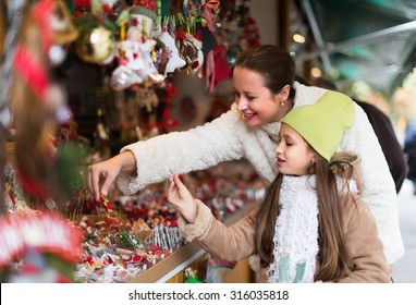 Smiling mother with positive girl in Christmas market. Focus on girl