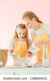 smiling mother pouring milk into dough while daughter kneading isolated on pink
