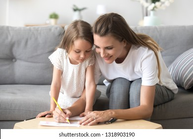Smiling mother with preschool daughter drawing with colored pencils, happy parent and child having fun together at home, sitting on cozy sofa in living room, teaching, paint picture