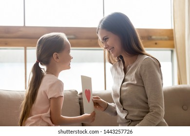 Smiling mother receiving gift from little adorable daughter at home, cute girl congratulating mum with mothers day or birthday, presenting postcard, sitting together on couch, family celebration