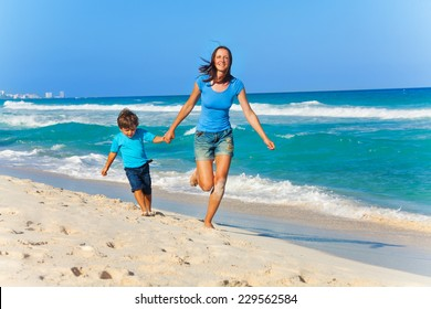 Smiling mother and son hold arms while running