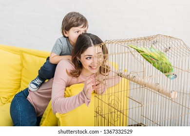 smiling mother and son looking at green parrot in bird cage at home