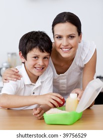 Smiling mother and son making the school lunch in the kitchen