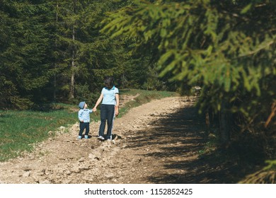 smiling mother and son walking and talking on stone path at forest