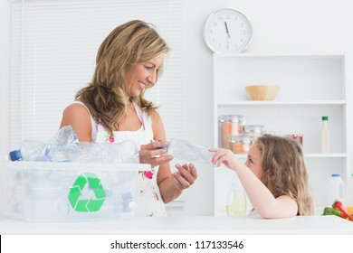 Smiling mother sorting waste with her daughter