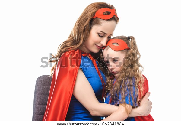 smiling mother in superhero costume hugging little daughter in mask and cloak isolated on white