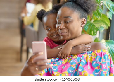 Smiling mother taking selfie with her cute little daughter. Looking at smartphone, feeling happy, satisfied, relaxed. Family hugs, lovely photo. Having good time. Sitting in cafe.
