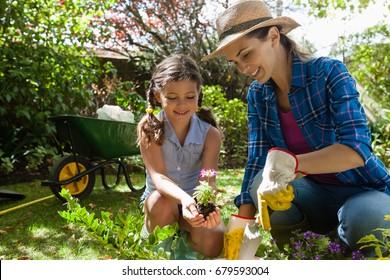 Smiling mother teaching daughter to plant seedlings while gardening in backyard