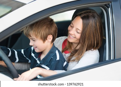 Smiling mother teaching her son how to drive a car