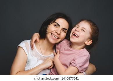 smiling mother tickling laughing girl at studio