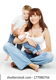 Smiling mother with two kids son and newborn baby, sitting over white background