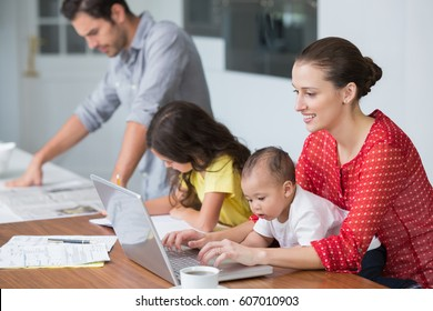 Smiling mother working on laptop with baby while daughter studying at desk