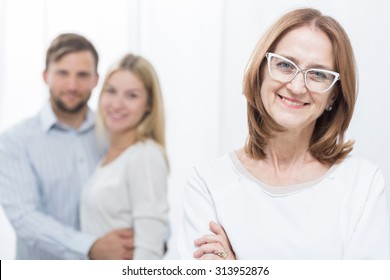 Smiling mother-in-law with happy family in background