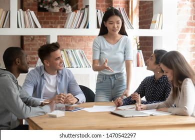 Smiling motivated asian female team leader holding meeting with diverse groupmates, explaining new project detail. African american, indian and caucasian concentrated students discussing assignment.