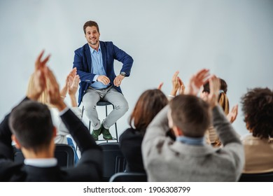 Smiling motivational speaker sitting in front of his audience who is clapping.