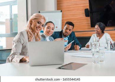 smiling multicultural businesspeople sitting in conference hall and looking at laptop
