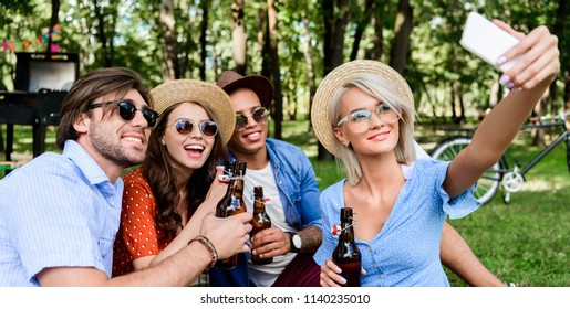 smiling multicultural friends with beer taking selfie on smartphone while resting in summer park