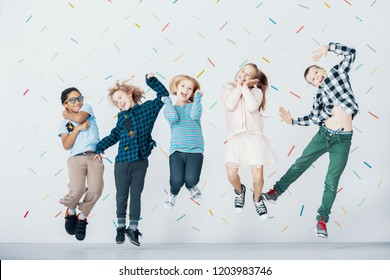 Smiling multicultural group of children jumping against colorful wallpaper