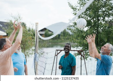 smiling multicultural old friends playing volleyball on beach on summer day