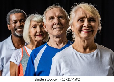 smiling multicultural senior sportspeople standing isolated on black