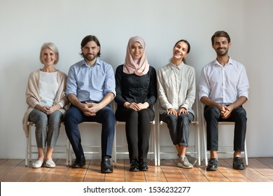 Smiling multicultural young and old professional business people sit on chairs in row looking at camera, happy staff job candidates group team portrait, human resource, diverse ethnicity concept