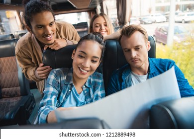 smiling multiculutral friends looking at map during trip on travel bus