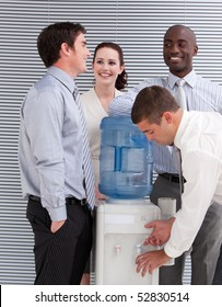Smiling multi-ethnic business people interacting at a watercooler in the office