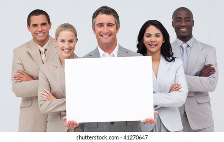 Smiling multi-ethnic business team holding a white card