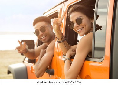 Smiling multiethnic couple sitting in a car and showing peace gesture outdoors