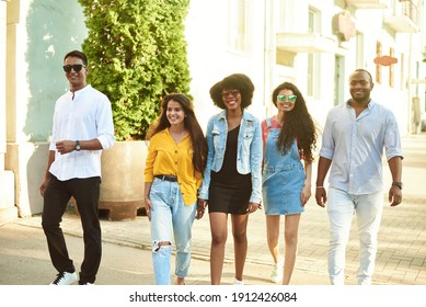 Smiling multiethnic diverse friends speak walking on the street. Communication concept