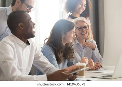 Smiling multiethnic employees sit at office desk laughing watching funny video training on laptop, happy diverse workers or businesspeople work together in office have fun during coffee break
