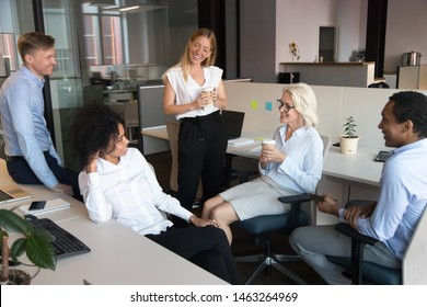 Smiling multiethnic employees talk and chat enjoy drinking coffee at office break, happy diverse colleagues have fun brainstorming discussing ideas at informal meeting in coworking open space