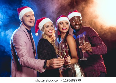 smiling multiethnic friends in santa hats clinking with champagne glasses on new year party