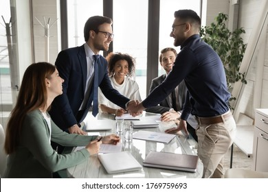 Smiling multiethnic male business partners shake hands close deal make agreement at team meeting in boardroom, excited diverse businessmen handshake get acquainted greeting at briefing in office