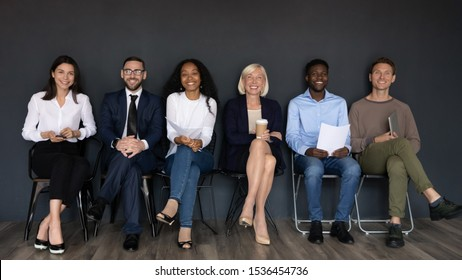 Smiling multiethnic professional formal businesspeople sit on chairs in row near black wall looking at camera, happy diverse ethnicity young old human resource staff group team portrait, hr concept