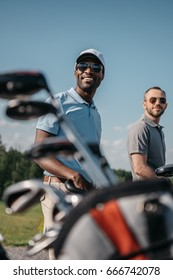 smiling multiethnic sportsmen going to the golf course, bag with clubs on foreground