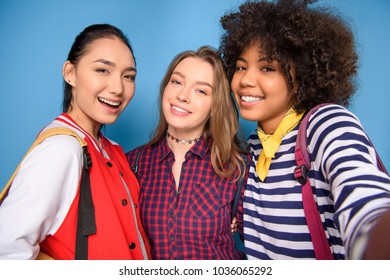 smiling multiethnic students taking selfie, isolated on blue