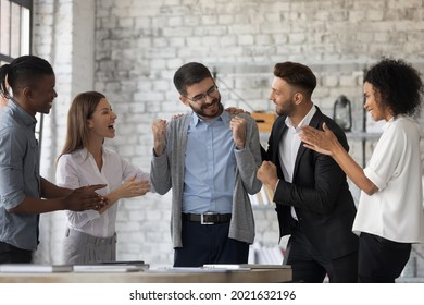 Smiling multiracial businesspeople congratulate colleague with job success or achievement. Happy supportive diverse multiethnic employees greet excited male worker with work promotion. - Shutterstock ID 2021632196