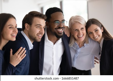 Smiling multiracial businesspeople embrace posing for group picture in office together, happy motivated diverse multiethnic colleagues coworkers show unity and support in work, teamwork concept
