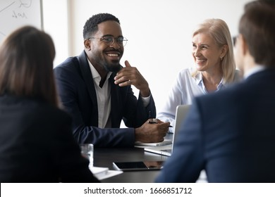 Smiling multiracial diverse businesspeople sit at office desk discussing business project together, happy multiethnic colleagues coworkers brainstorm talk consider cooperation in boardroom