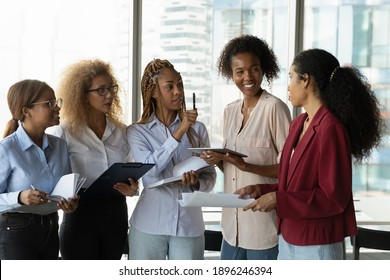 Smiling multiracial diverse female colleagues coworkers stand in office talk brainstorm over company paperwork. Happy multiethnic women engaged in discussion at casual meeting at workplace.