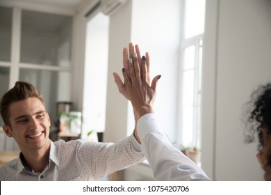 Smiling multiracial man and woman giving high five celebrating victory sharing success and good teamwork result concept, happy motivated friends, coworkers or students excited by goal achievement