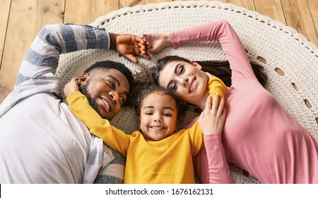 Smiling multiracial millennial family lie on the floor top view, panorama