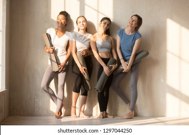 Smiling multiracial sportive girls pose near sunny wall holding yoga mats in hands, happy diverse toned women in sport leggings and bra wait for workout with training facilities. Healthy life concept