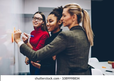 Smiling multiracial women colleagues standing near flip chart for drawing graphic of productivity cooperating on project,crew of divercity female partners planning strategy with professional coach