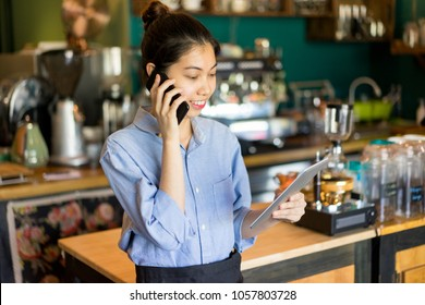 Smiling multi-tasking manager working in restaurant. Smiling confident small business owner talking on phone and viewing notes on tablet. Cafe concept