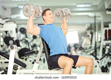 Smiling muscular guy lifting weights in a gym