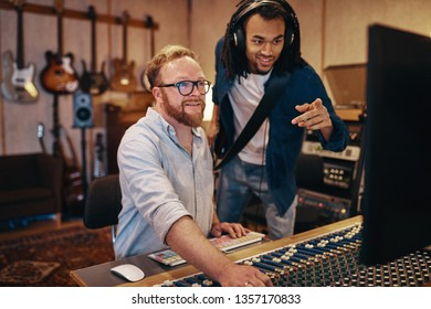 Smiling music producer and a young African American musician with a guitar talking together over a soundboard in a recording studio