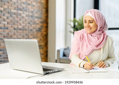 Smiling muslim businesswoman taking notes sitting at the desk in modern office space. Young islamic female student wearing hijab and smart casual wear overwrites from the laptop screen into notebook