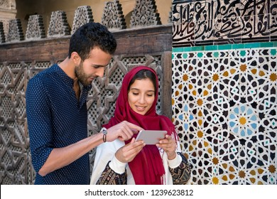 Smiling muslim couple looking at cellphone beside the arabesque decorated moroccan wall